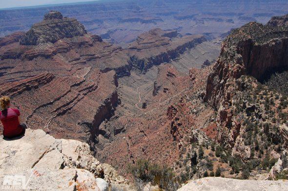 Hiker sitting on a million foot drop off.
