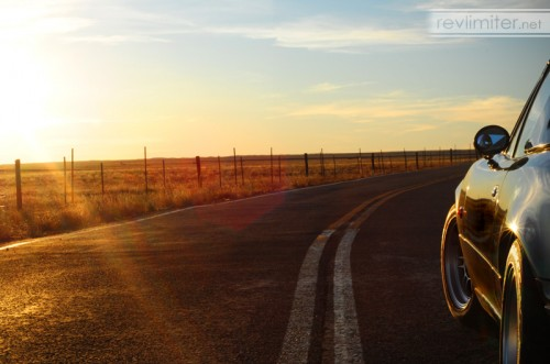 Sunset, a long road, and a small car.
